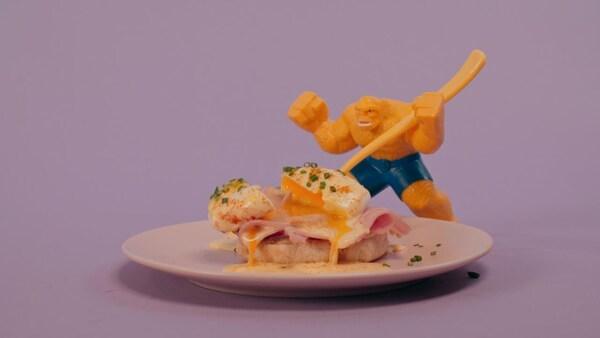 Un œuf mollet est posé sur une tranche de jambon et de pain.