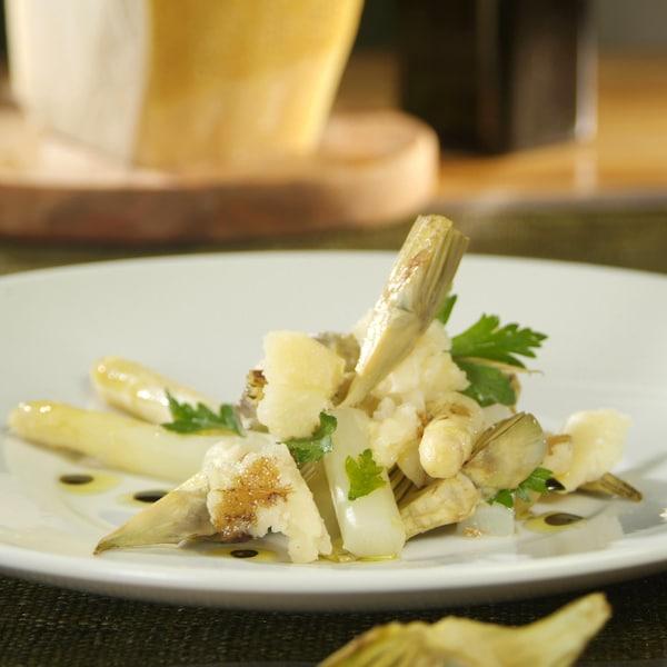 Asperges blanches et artichauts en salade dans une assiette.