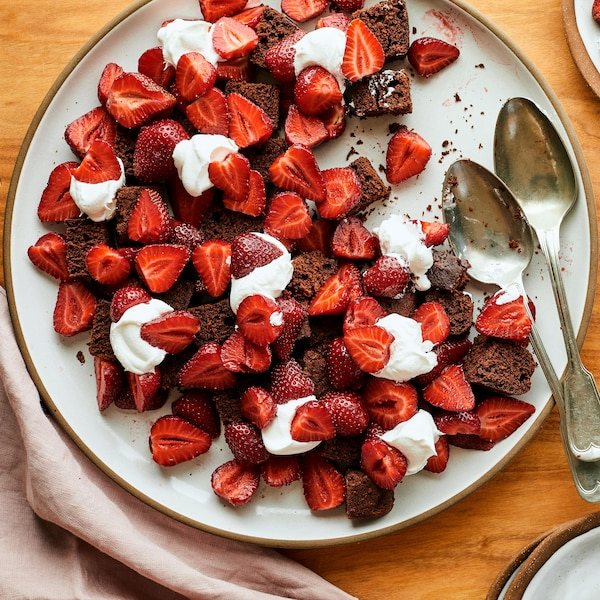Sur une table en bois, est déposé une grande et deux petites assiettes contenant de la bagatelle choco-café aux fraises.