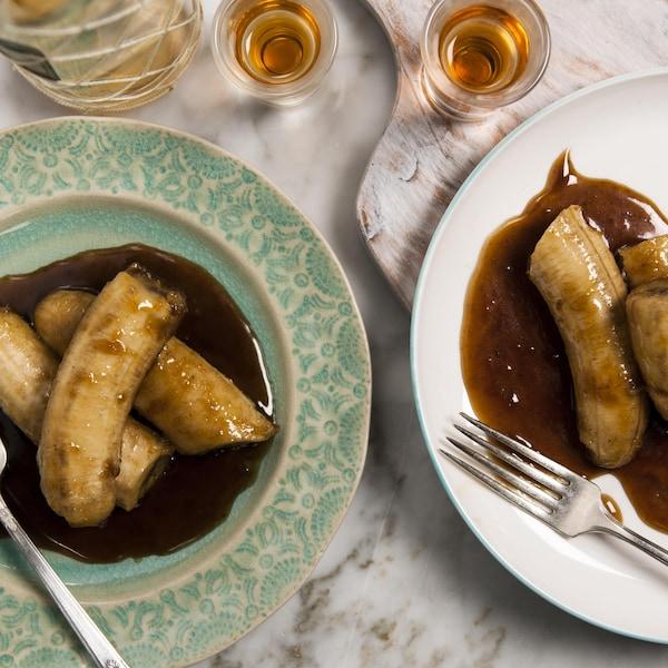 Deux assiettes de bananes flambées nappées de leur jus de cuisson.