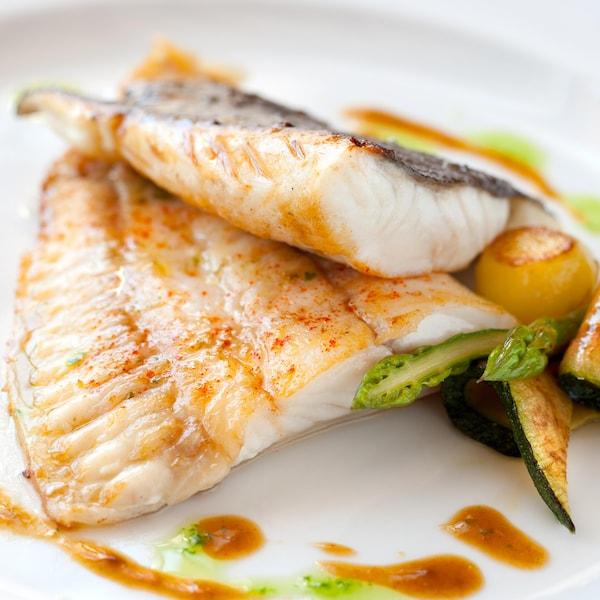 Deux morceaux de poisson et des légumes dans une assiette.