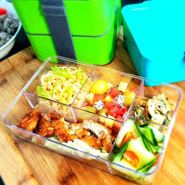 Une boîte repas compartimentée remplie d'aliments.