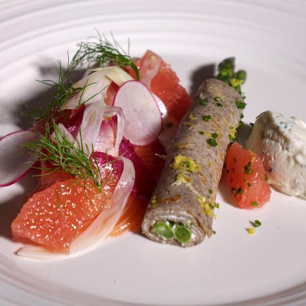 Un morceau de saumon recouvert de morceaux de pamplemousse, de radis et d'aneth avec une petite crêpe roulée avec des asperges à l'intérieur et de la crème fraîche au raifort.