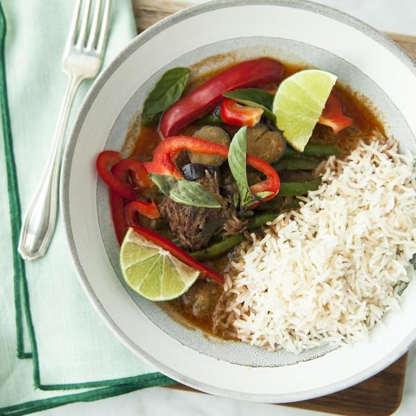 Un bol de boeuf braisé au car rouge servi avec du riz et des quartiers de lime.