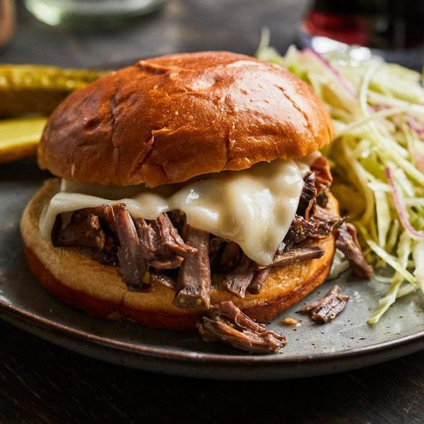 Un burger au bœuf effiloché et fromage dans une assiette.