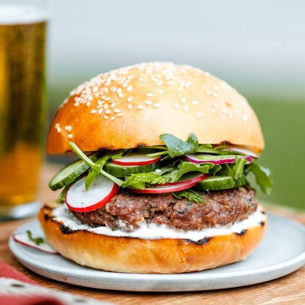 Un burger au bœuf avec des concombres, des radis, de la roquette et une sauce au yogourt.
