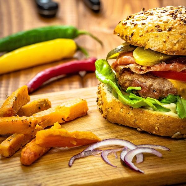 Un burger de boeuf au cheddar et frites de patate douce sur une planche de bois.