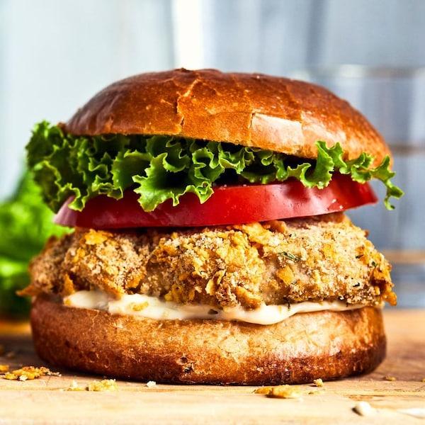 Un burger au poulet croustillant garni de tomates, de salade et d'une sauce.