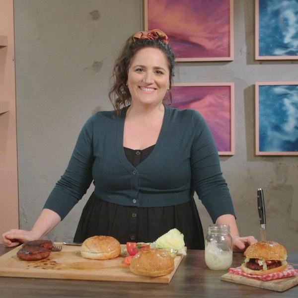 Sur une planche à découper, deux galettes végétaliennes et deux pains à hamburger ont   été posés.