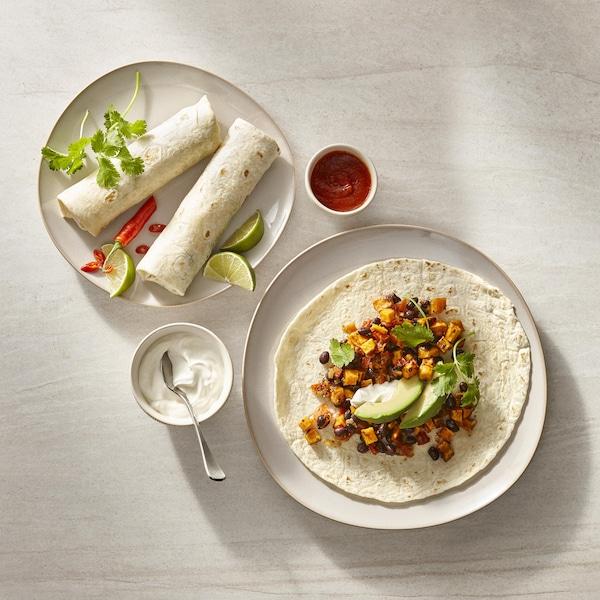 Des assiettes avec des burritos d'haricots et leurs accompagnement.