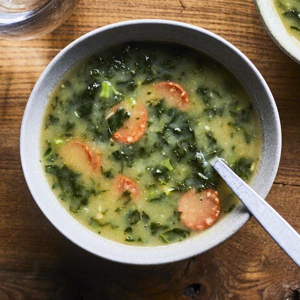 Un bol de soupe avec des carottes et du chou.