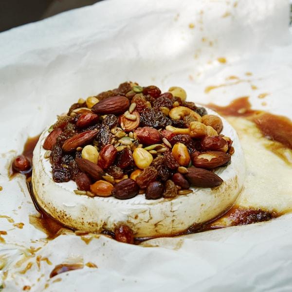 Sur un papier parchemin, est déposé un fromage camembert. Sur le dessus du fromage, est déposé le mélange du randonneur et le sirop d'érable.