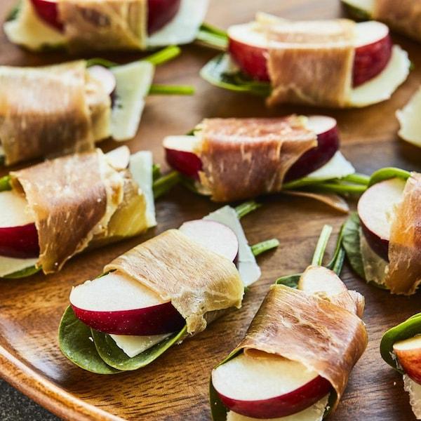 Des canapés de pommes au prosciutto disposés sur un plateau.