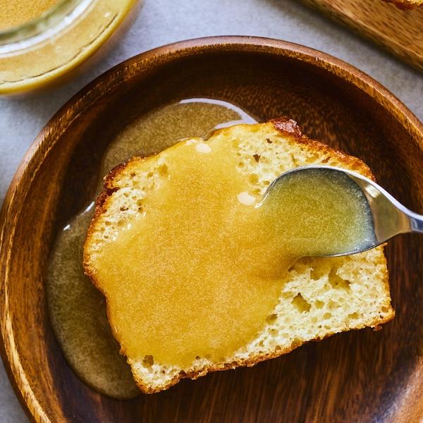 Cuillère qui verse du caramel sur une tranche de gâteau à la vanille dans une assiette.