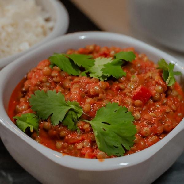 Un bol de cari rouge de lentilles garni de coriandre fraîche, servi avec un bol de riz.