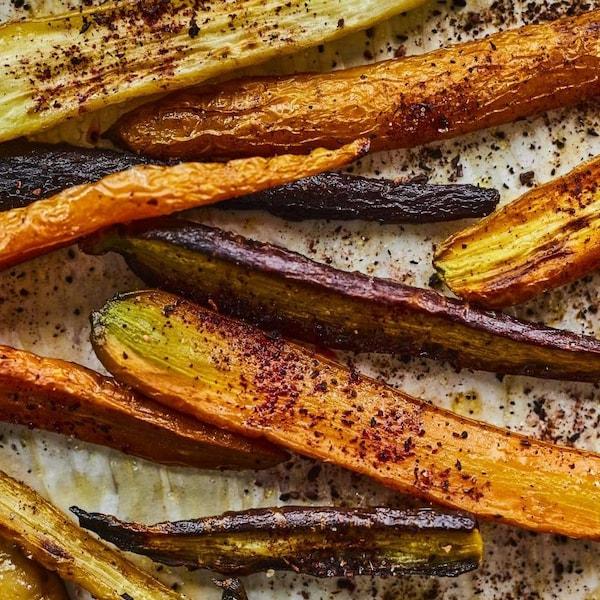 Des carottes coupées sur la longueur, rôties et garnies de sel d'hibiscus, sur une plaque de cuisson.