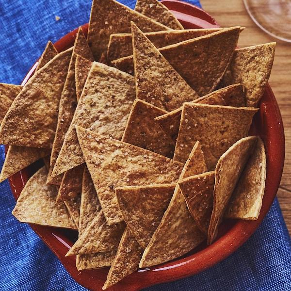 Un bol de chips de tortilla et un bol de salsa maison, sur une table de bois avec un linge de cuisine.