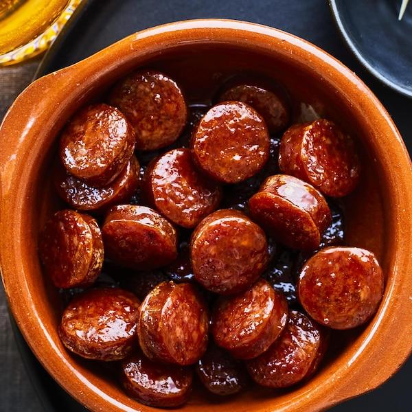 Bol rempli de tranches de chorizo caramélisées à l'érable et servi avec des olives.
