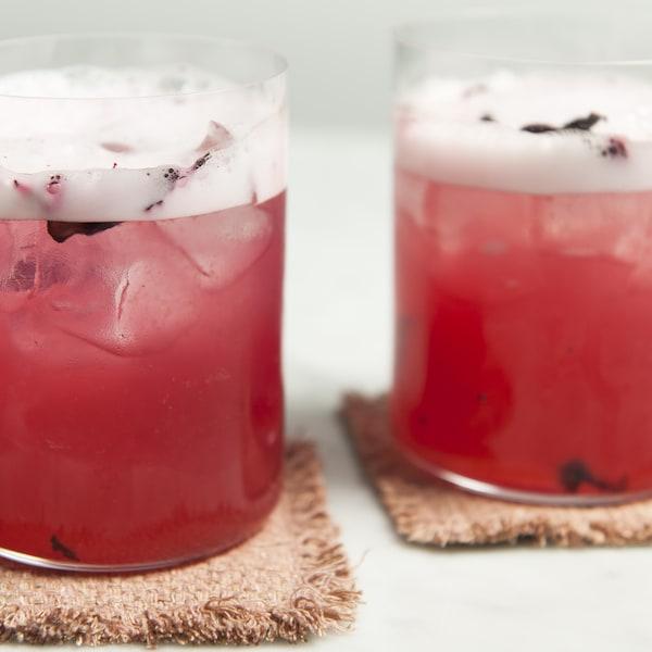 Deux verres de cocktail La Rosée servies sur des sous-verre en jute.