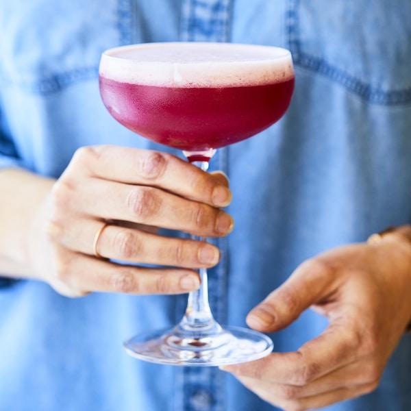 Femme portant une chemise en jeans et qui tient une coupe à cocktail.