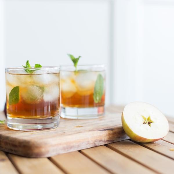 Deux verres remplis d'un cocktail à la pomme avec des feuilles de menthe.