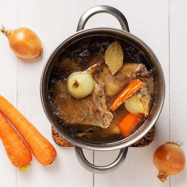 Un chaudron de consommé de boeuf, avec des carottes et des oignons.
