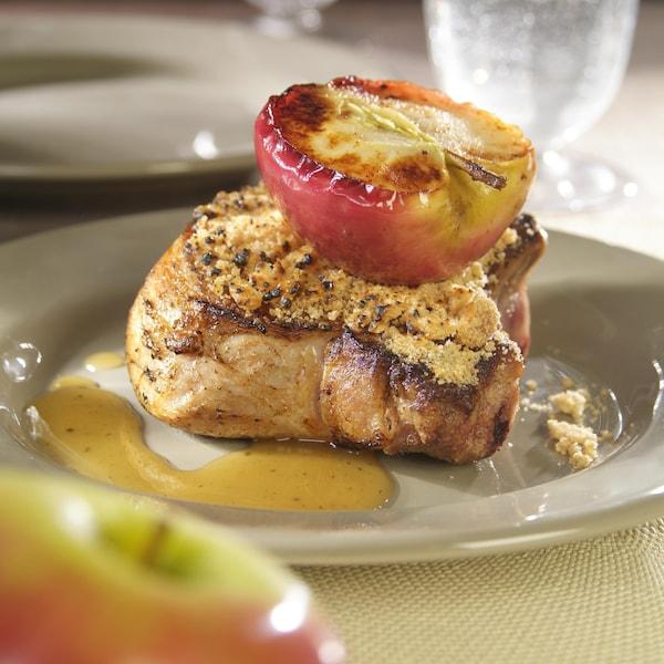 Un morceau de côte de porc garni d'une moitié de pomme et de sucre d'érable.