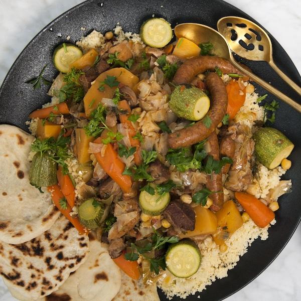 Une assiette de couscous royal servie avec du pain maison et de condiments.