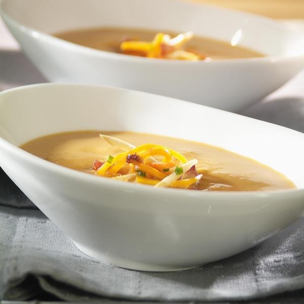 Un bol rempli de crème de fèves au lard jaune et garnie d'une fine brunoise de légumes orangés.
