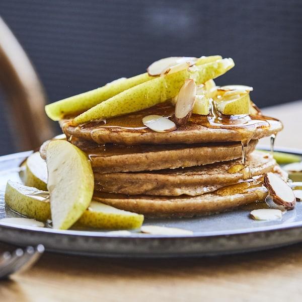 Une pile de quatre crêpes dans une assiette avec des morceaux de poires, d'amandes et du sirop d'érable.