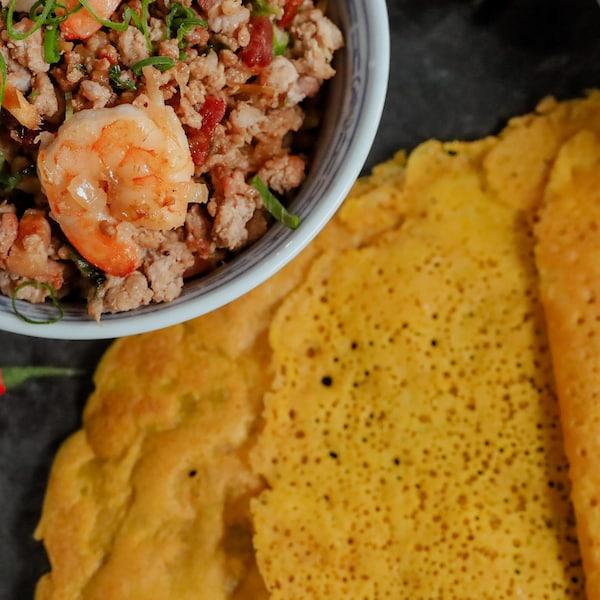 Une pile de crêpes croustillantes servies avec un bol de farce porc et crevettes.