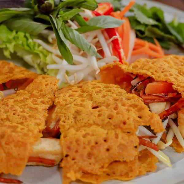 Des tranches de crêpes vietnamiennes farcies, accompagnées d'herbes fraîches, de légumes marinés et de fèves germées.