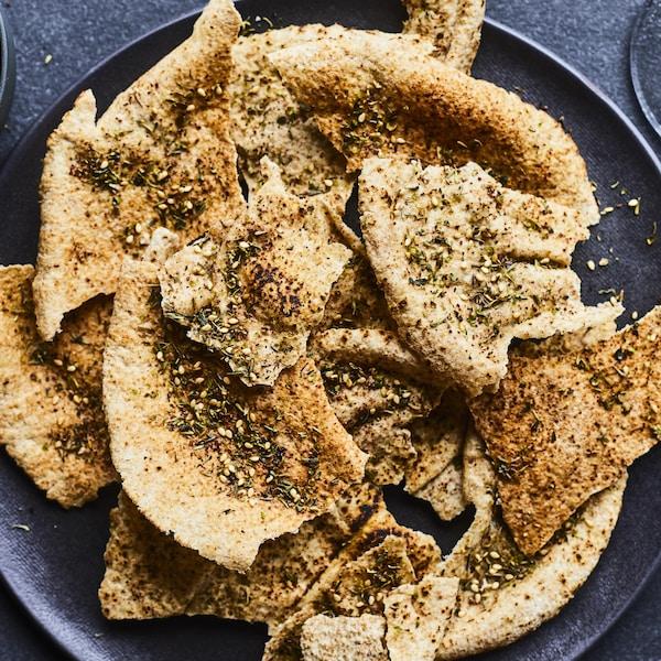 Des croustilles de pita au zaatar dans une assiette noire.