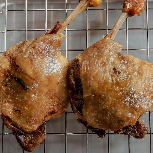 Deux cuisses de canard confites qui reposent sur une plaque de refroidissement.