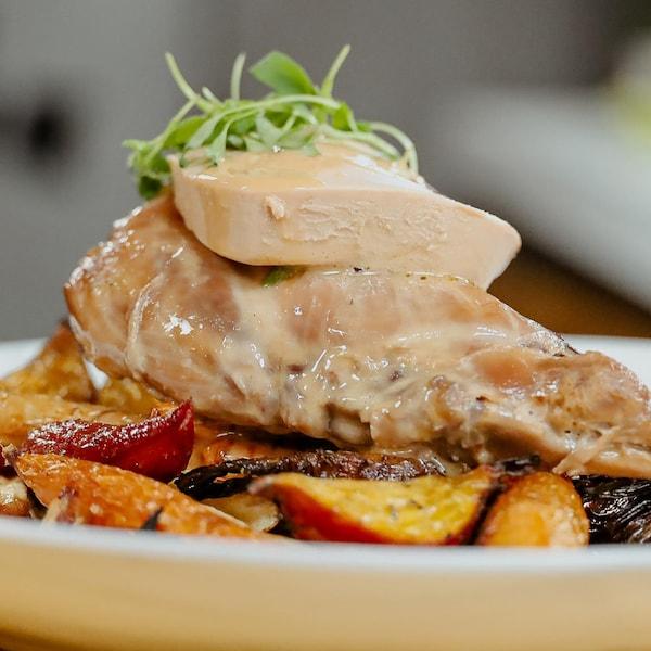 Cuisse de lapin braisée servie sur des pommes de terre et garnie d'une tranche de foie gras.