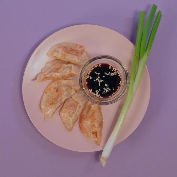 Cinq dumplings dans une assiette avec un petit bol de sauce et une branche d'oignon vert.
