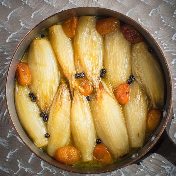 Une casserole d'endives confites avec des kumquuats et des baies de genièvre.