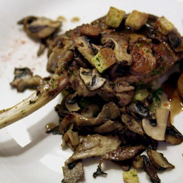 Un morceau de viande recouvert de légumes et de sauce.