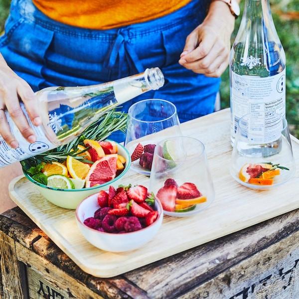Sur un coffre en bois, un bol contenant des framboises et des fraises tranchées en quartier et un autre  bol  contenant des agrumes sont prêts à être déposés dans des verres. Une personne verse de l'eau minérale dans un verre en verre contenant des tranches d'agrumes, des framboises et des fraises.
