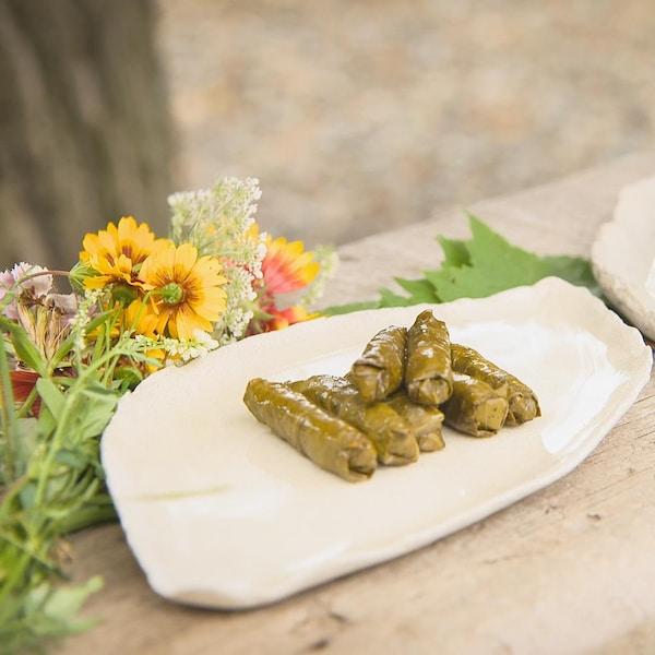 Des feuilles de vigne farcies dans une assiette et un bouquet de fleurs.