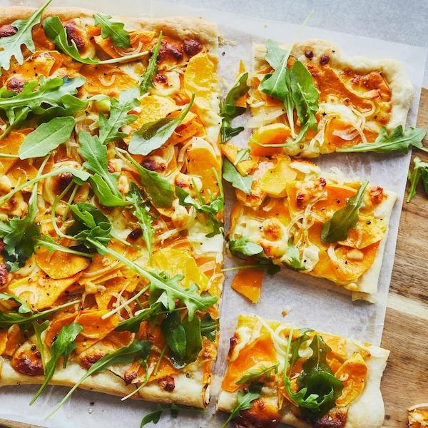 Focaccia à la courge et au fromage en grain servie sur une planche de bois.