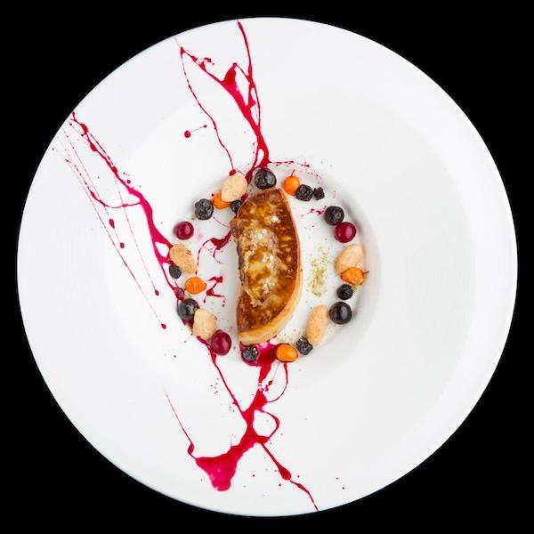 Une assiette de foie gras poêlé entouré de petits fruits.