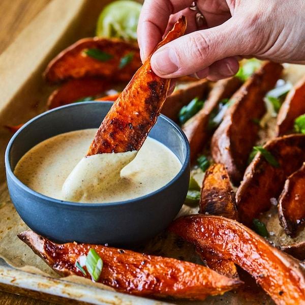 Des frites de patates douces qui sortent du four avec un petit bol de mayo au cari.