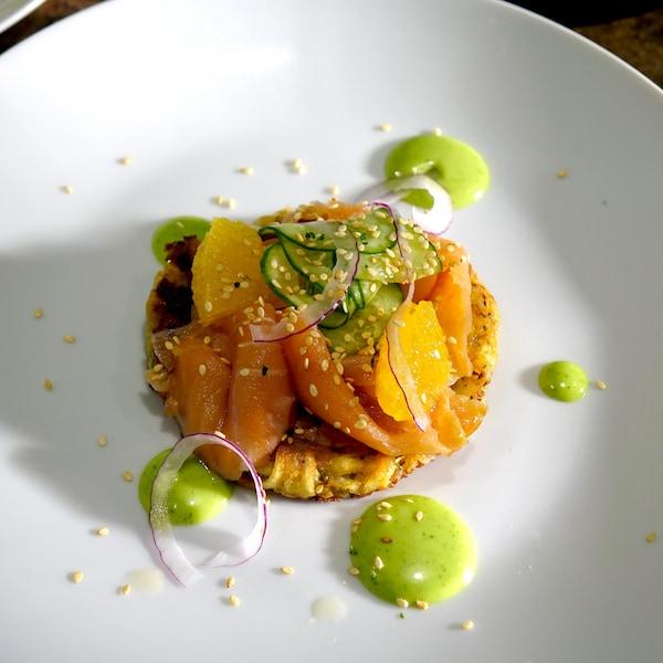 Une galette de pommes de terre recouverte de saumon fumé, de concombre et d'orange avec une mayonnaise au wasabi.