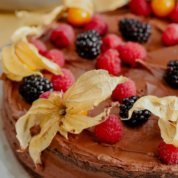 Un gâteau au chocolat garni de mûres, de framboises et de cerises de terre.