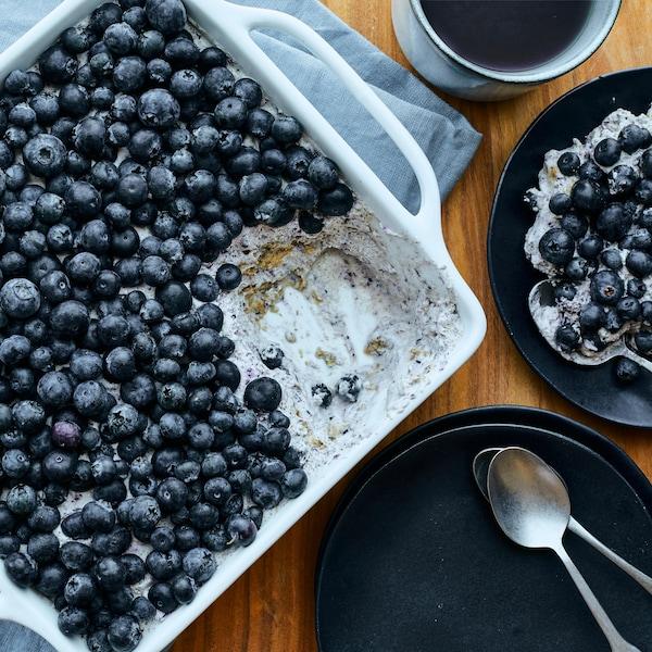 Un plat de service rempli de gâteau-frigo aux bleuets, avec une assiette servie, une théière et une tasse de thé à côté.
