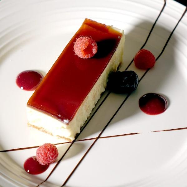 Un morceau rectangulaire de gâteau au fromage décoré avec quelques framboises.