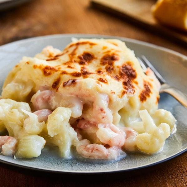 Un morceau de gratin de chou-fleur aux crevettes nordiques dans une assiette.
