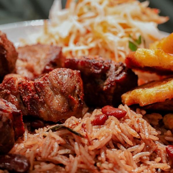 Du griot servi avec une portion de riz aux pois et du pikliz.