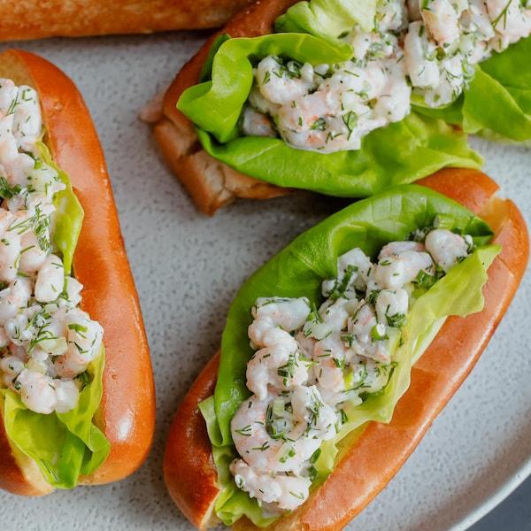 Des guédilles aux crevettes nordiques, garnies d'une feuille de laitue Boston et servies dans une assiette.